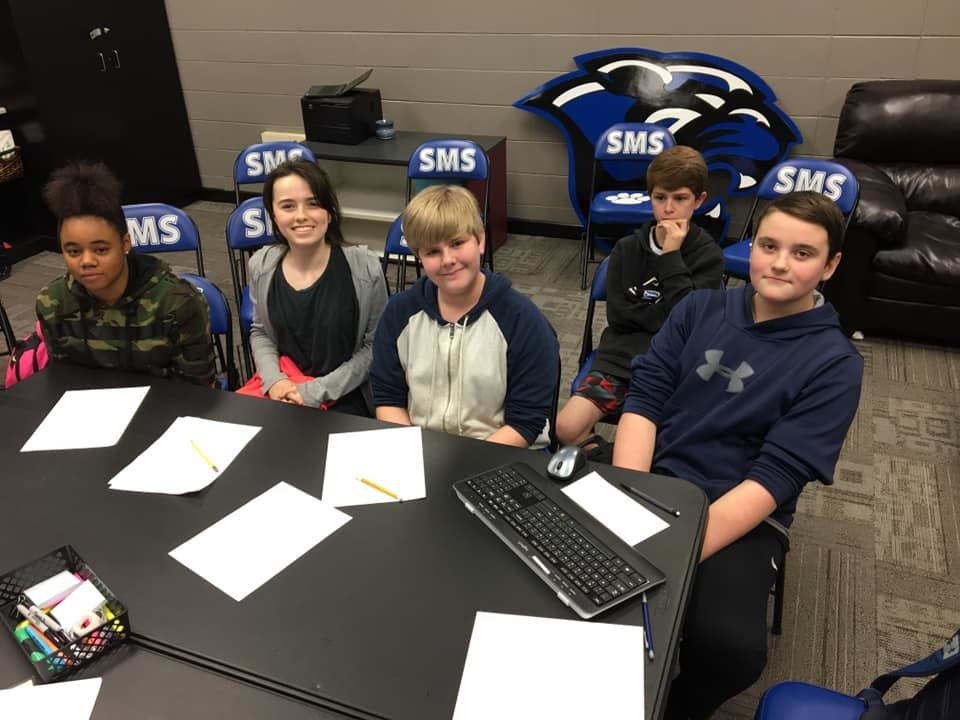 Students sit at a desk participating in math team